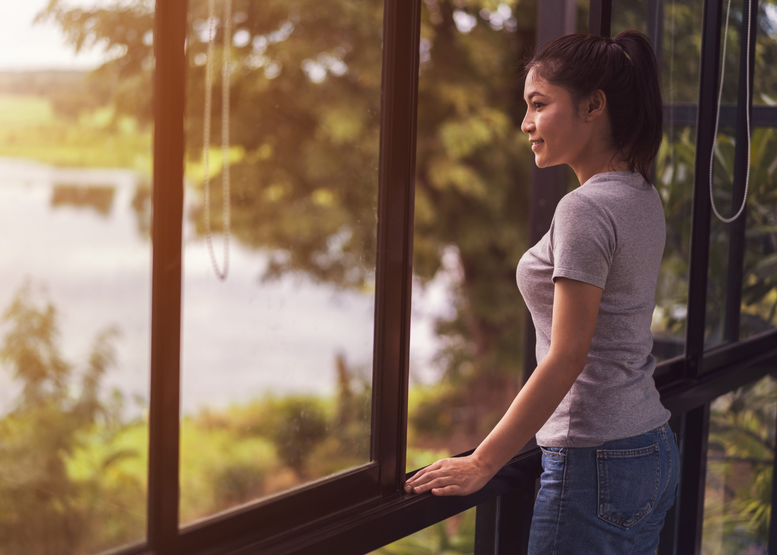 Young woman looking through window at a lake. Link takes you to the Bank of Versailles Checking and Savings Accounts page.