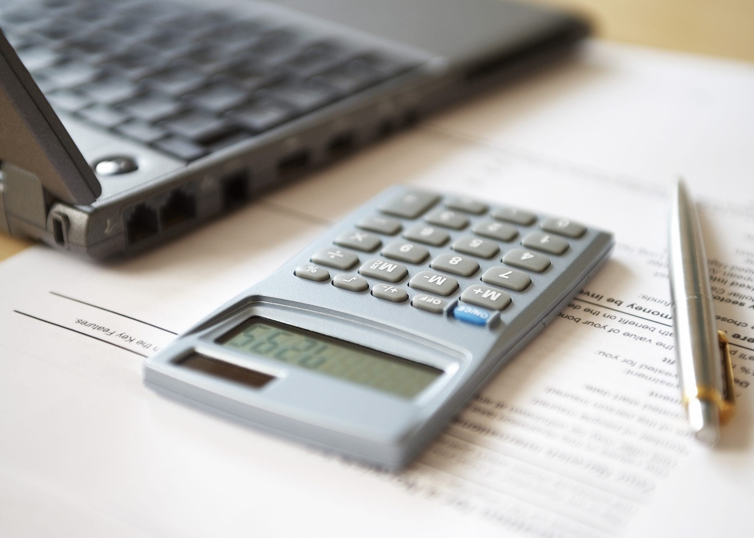 Image of a calculator, pen, paperwork, and laptop. Link takes you to the Bank of Versailles Certificates of Deposit page.
