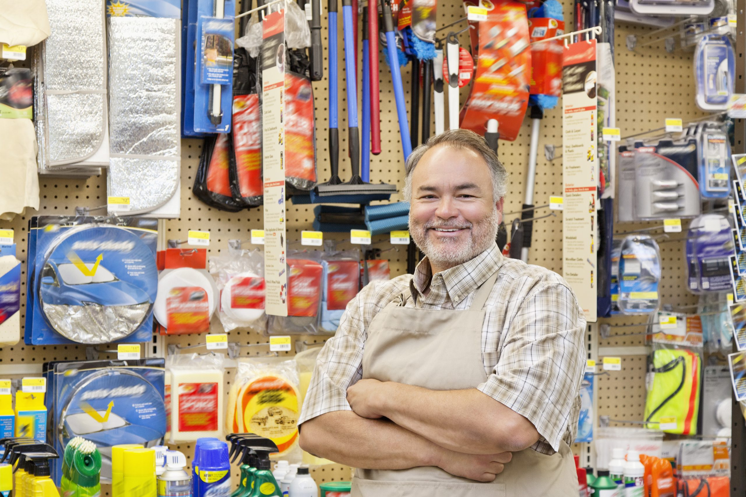 Business owner smiling in front of merchandise.