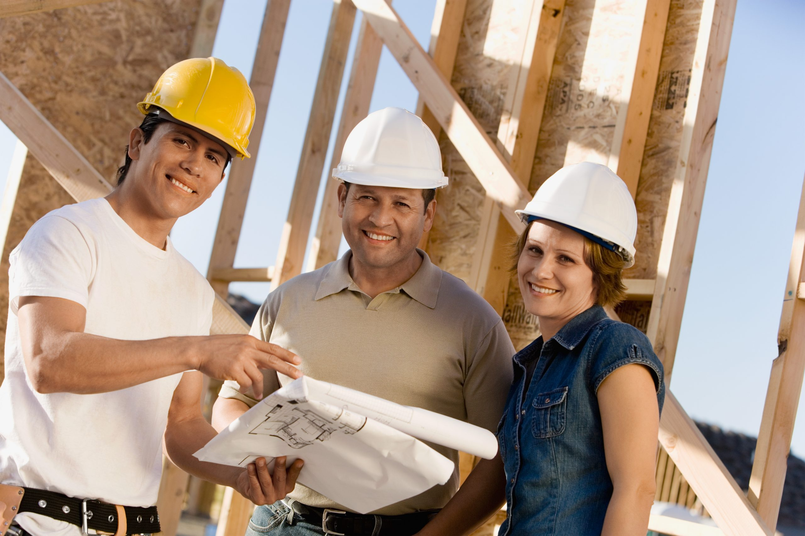 Builder and home owners reviewing home construction plans.