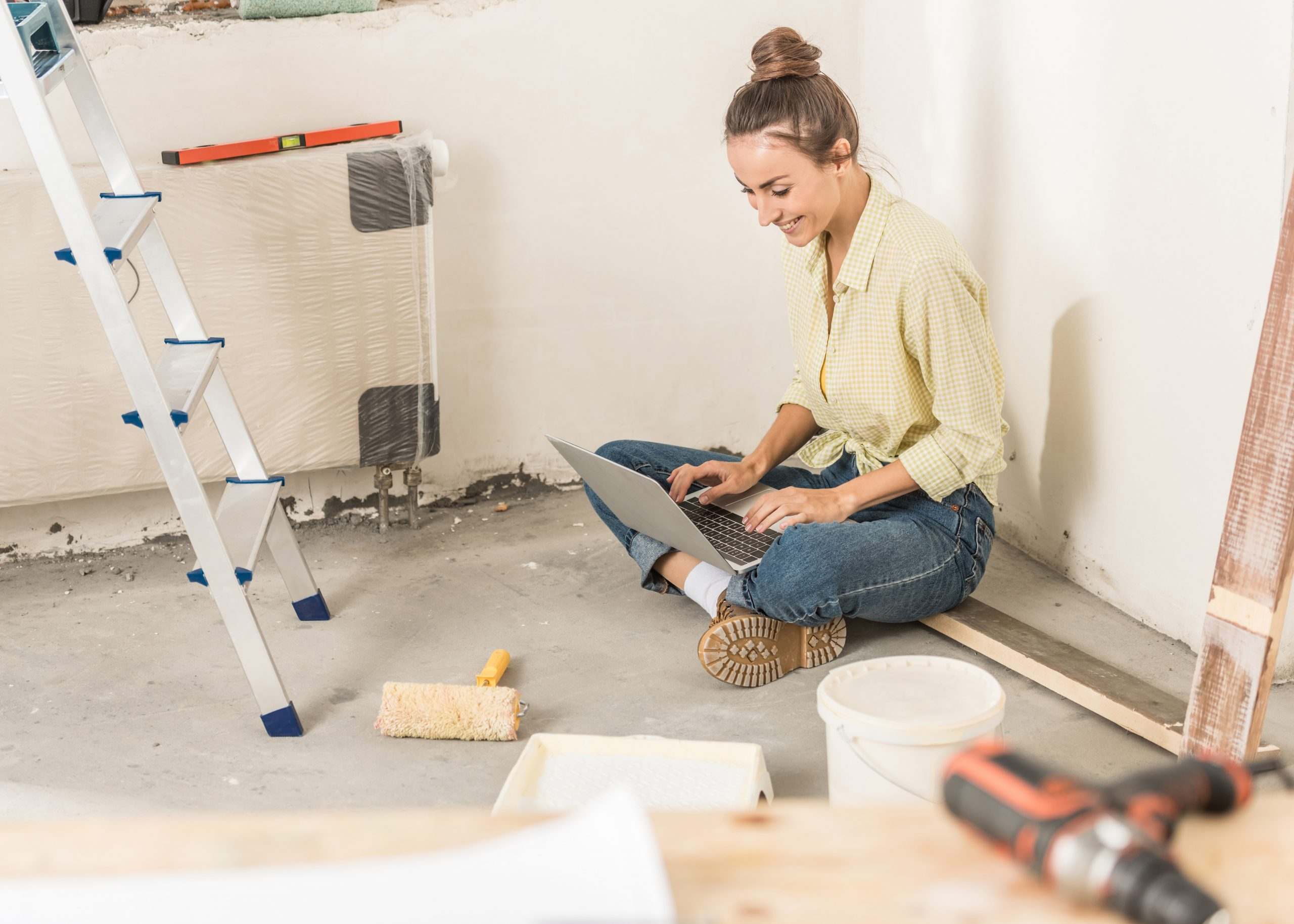 Young Caucasian woman sitting on the floor of a room being remodeled, using a laptop.