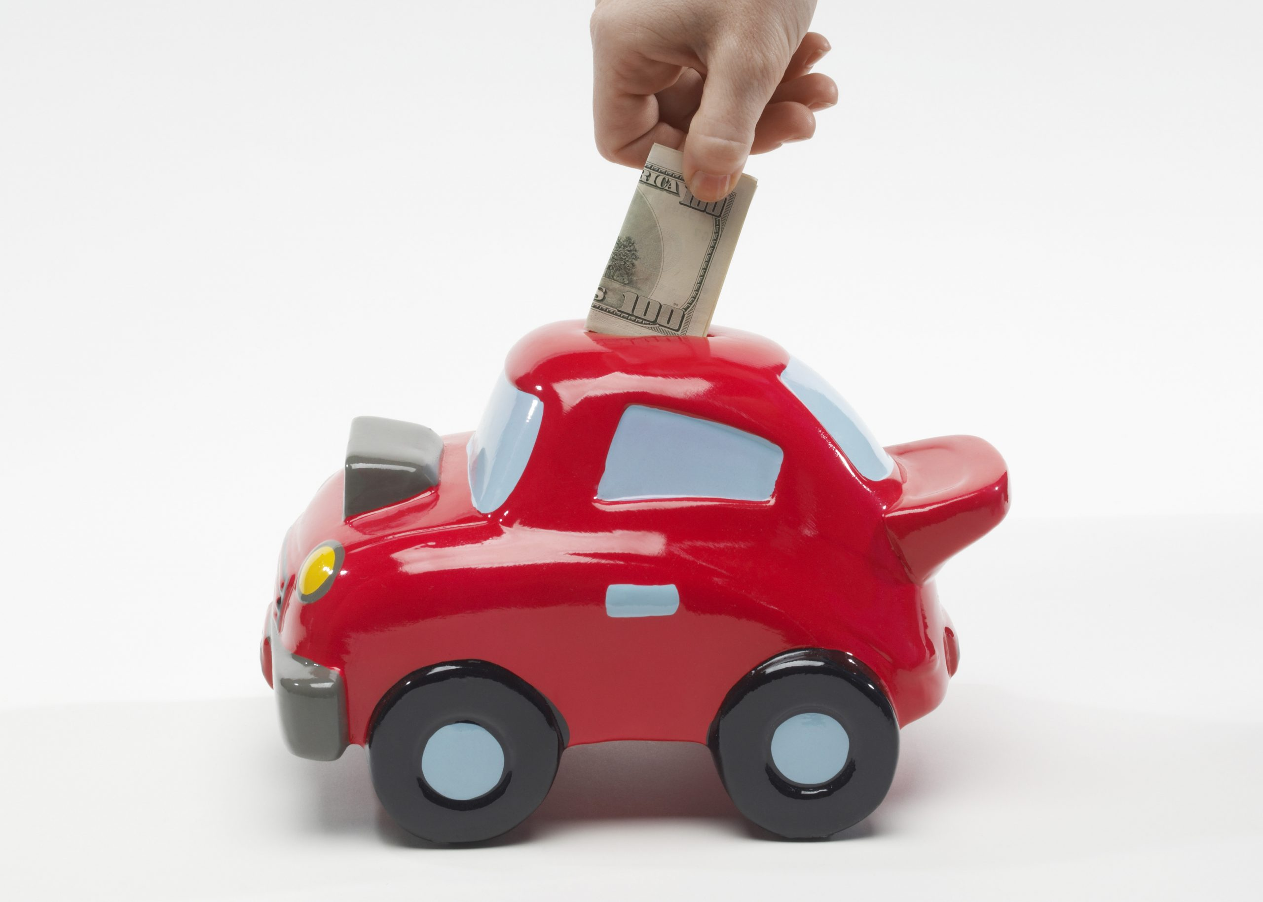 Image of a hand putting a $100 bill into a car shaped piggy bank. Link takes you the Bank of Versailles Passbook Savings Account page.