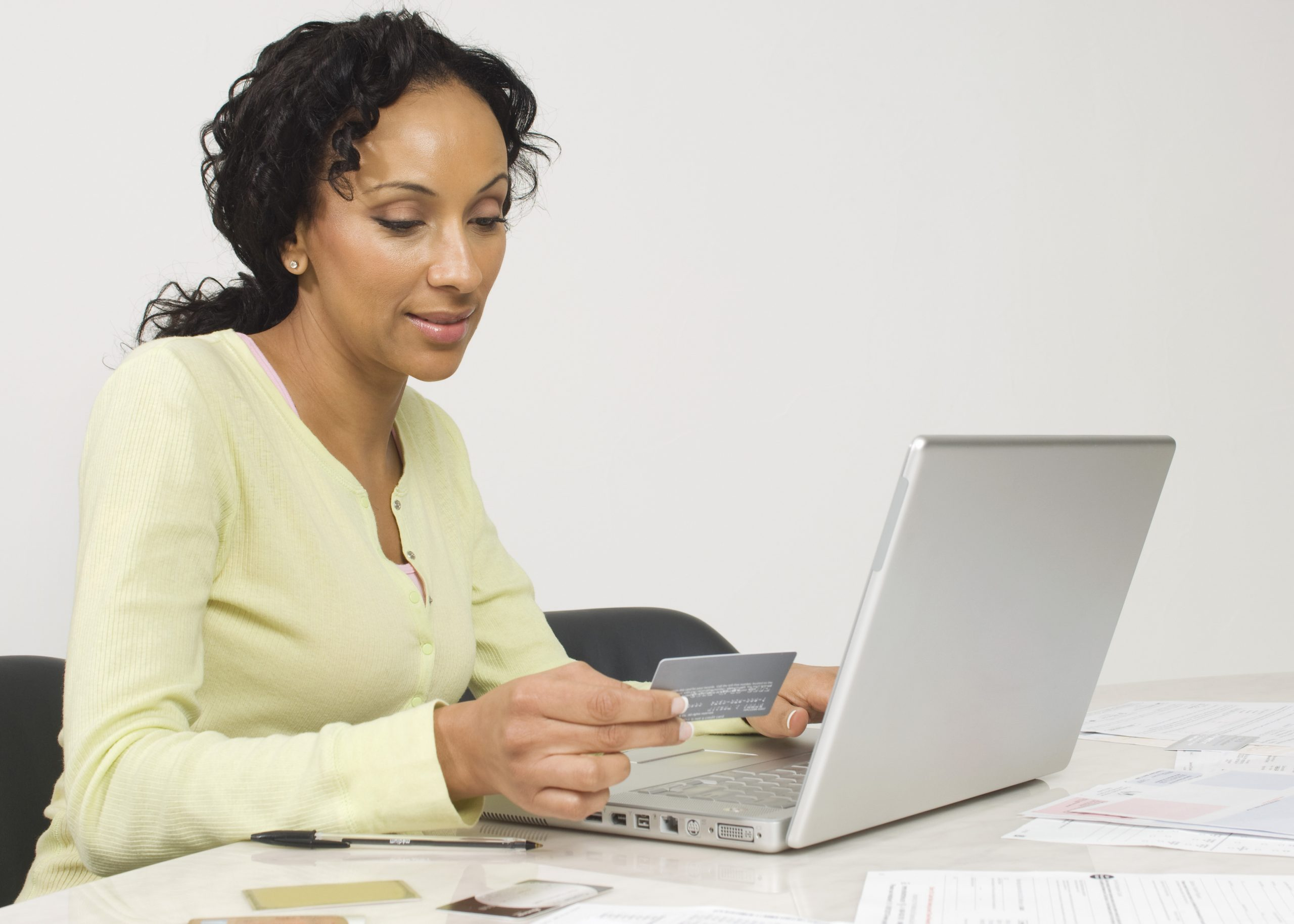 Adult woman using laptop and debit card. Link takes you to the Bank of Versailles Tiered Checking page.