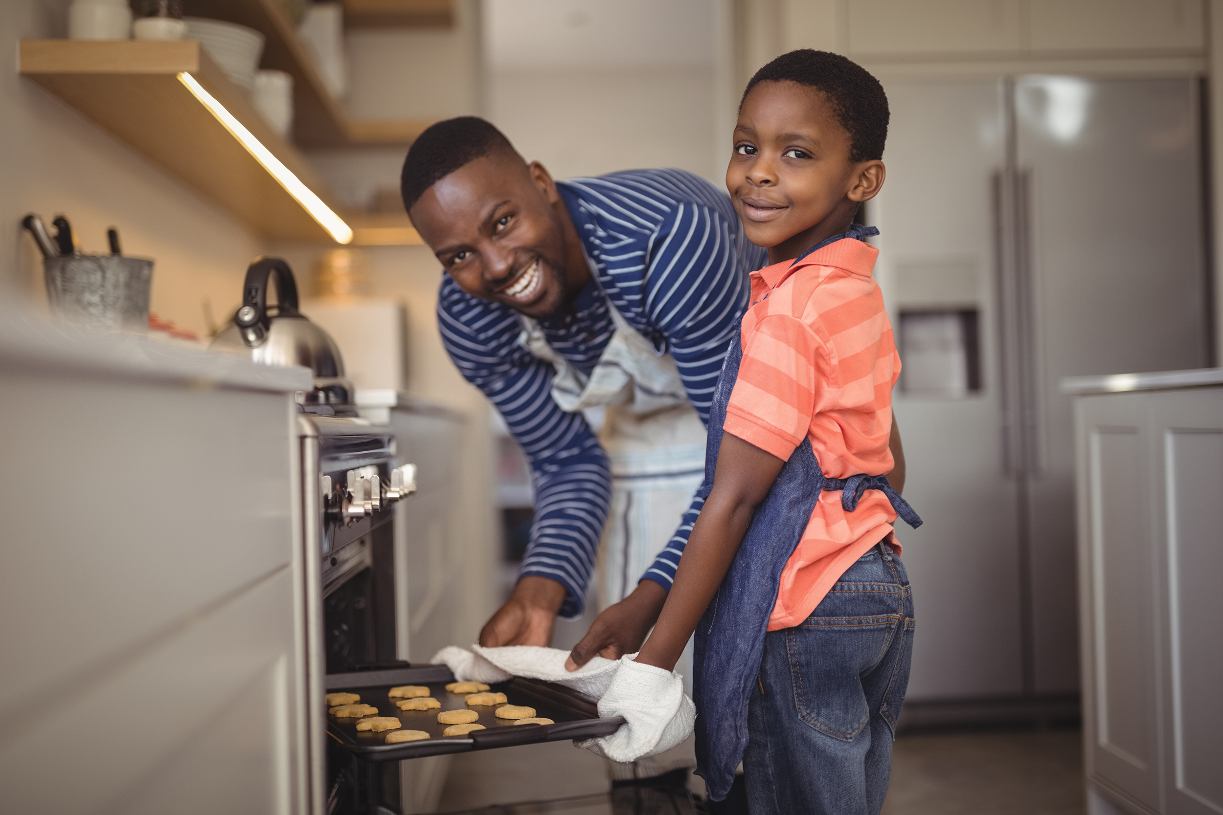 African American father and son in the kitchen baking cookies.